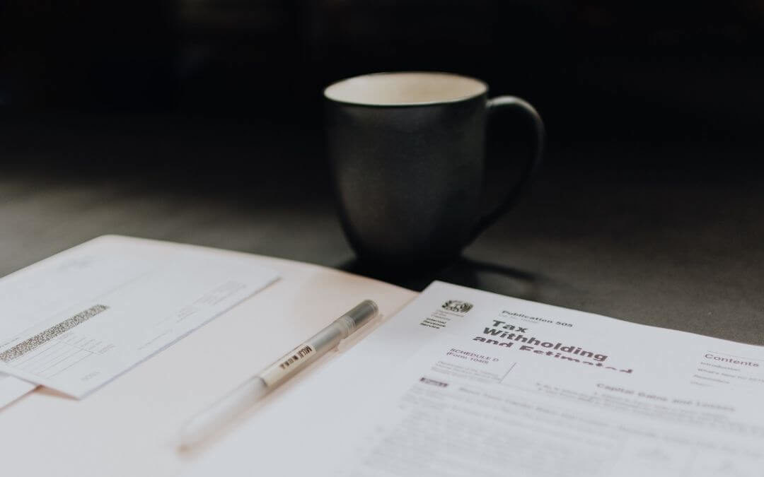 Tax forms and a mug of coffee